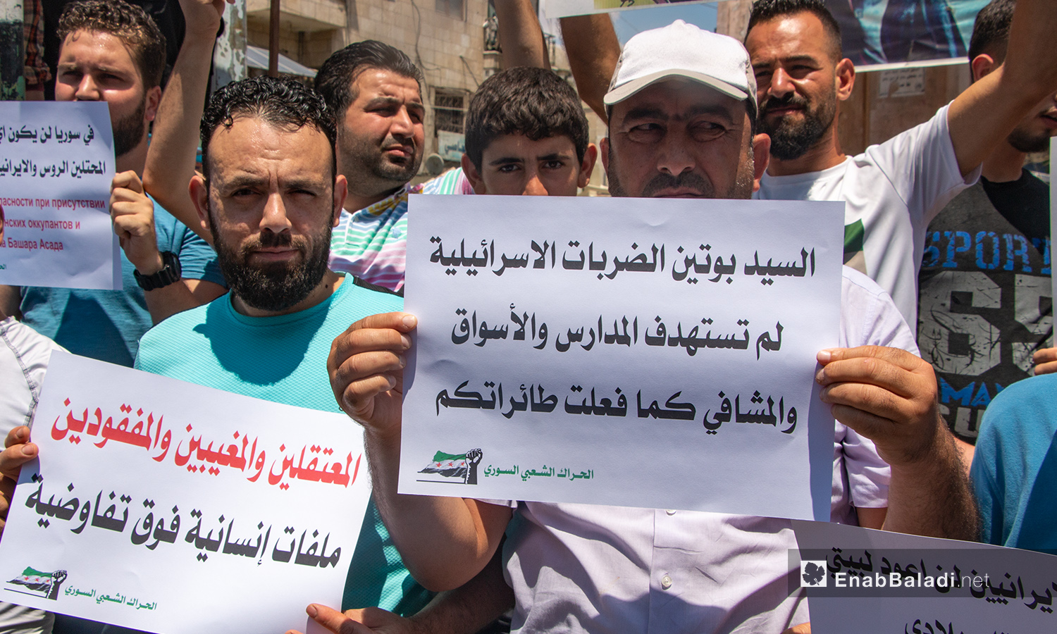 A man carrying a sign in which he addresses the Russian President Vladimir Putin. The sign says (Mr. Putin, the Israeli strikes did not target the schools, markets, and hospitals as the Russian warplanes did) – 03 July 2020 (Enab Baladi / Anas al-Khouli)