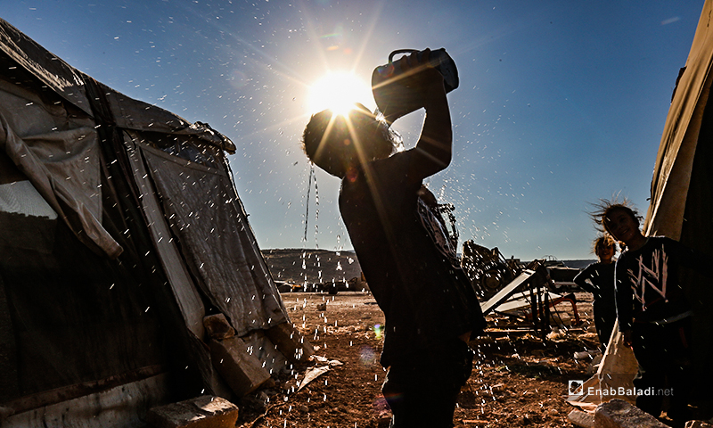 A child washing his face to reduce the summer heat in the IDPs camps of northern Idlib countryside – 07 July 2020 (Enab Baladi / Yousef Ghuraibi)