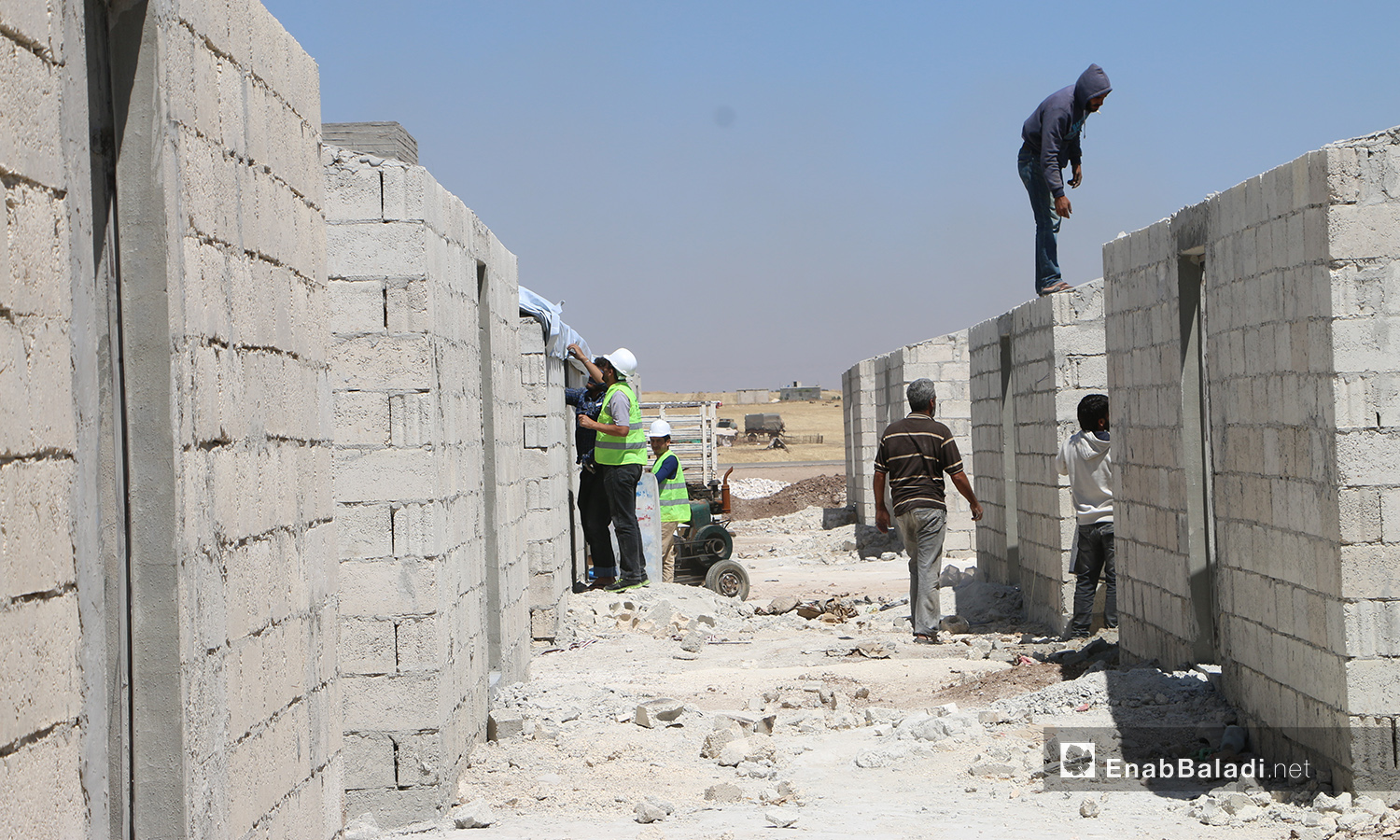 The construction workers of the concrete housing units project to replace the makeshift tents. This project is conducted by humanitarian organizations and bodies operating in northern Syria in Bahorta village of northern Aleppo countryside – 26 June 2020 (Enab Baladi / Abdul Salam Majan)
