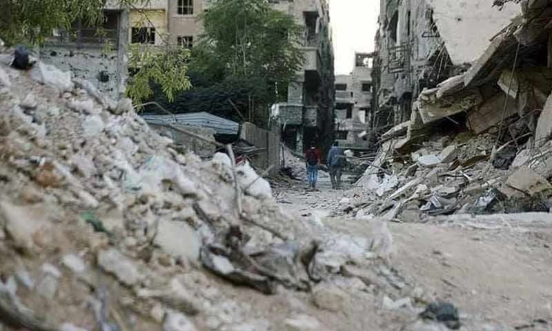 Two citizens walking through the rubble of the Yarmouk Camp 2018 (Yarmouk Camp News)