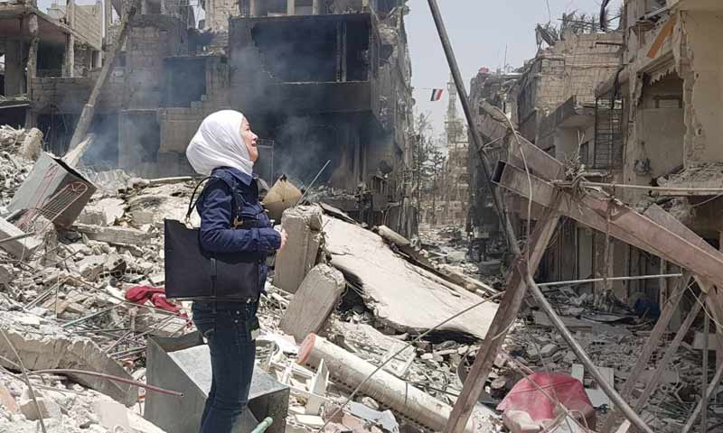 A woman standing in front of the rubble of her destroyed house in the Yarmouk Camp - 2018 (Yarmouk Camp News)
