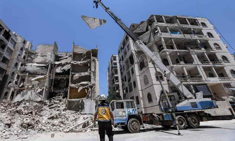 """Syria's Civil Defence teams in Idlib remove the debris from the roof of a partially destroyed building for fear of its fall- 12 July 2020 ( """"This is Idlib"""" Facebook page)"""
