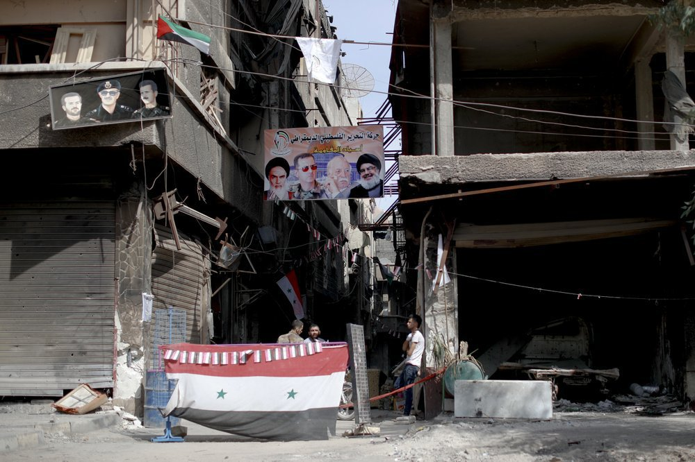 """A group of men at a checkpoint sitting under the poster of """"Leaders of the Resistance"""" of the Iranian founder, Ayatollah Khomeini, the head of the Syrian regime Bashar al-Assad, Ahmed Jibril and Hassan Nasrallah in the Yarmouk camp (AP)"""