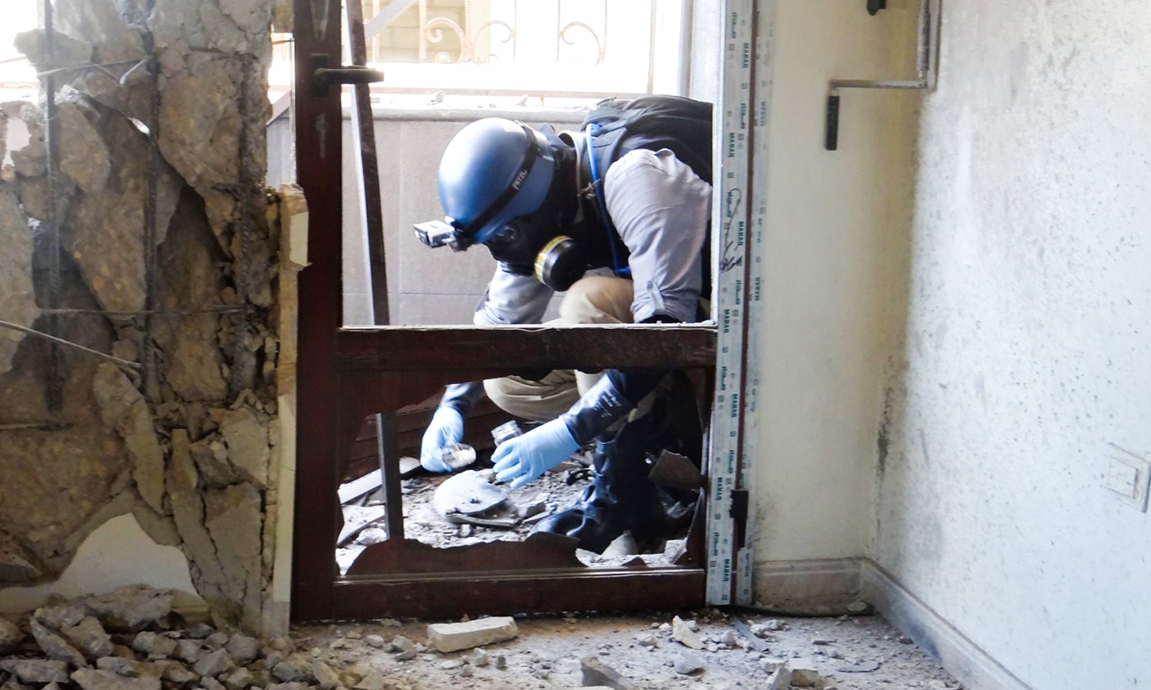 A UN expert collecting samples to investigate the chemical weapons attack in Eastern Ghouta - 2013 (AFP)