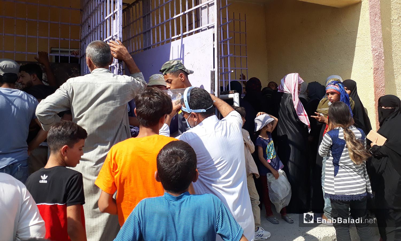 Syrian citizens overcrowded at a bakery in al-Raqqa city – 06 August 2020 (Enab Baladi / Abdul Aziz al-Saleh)