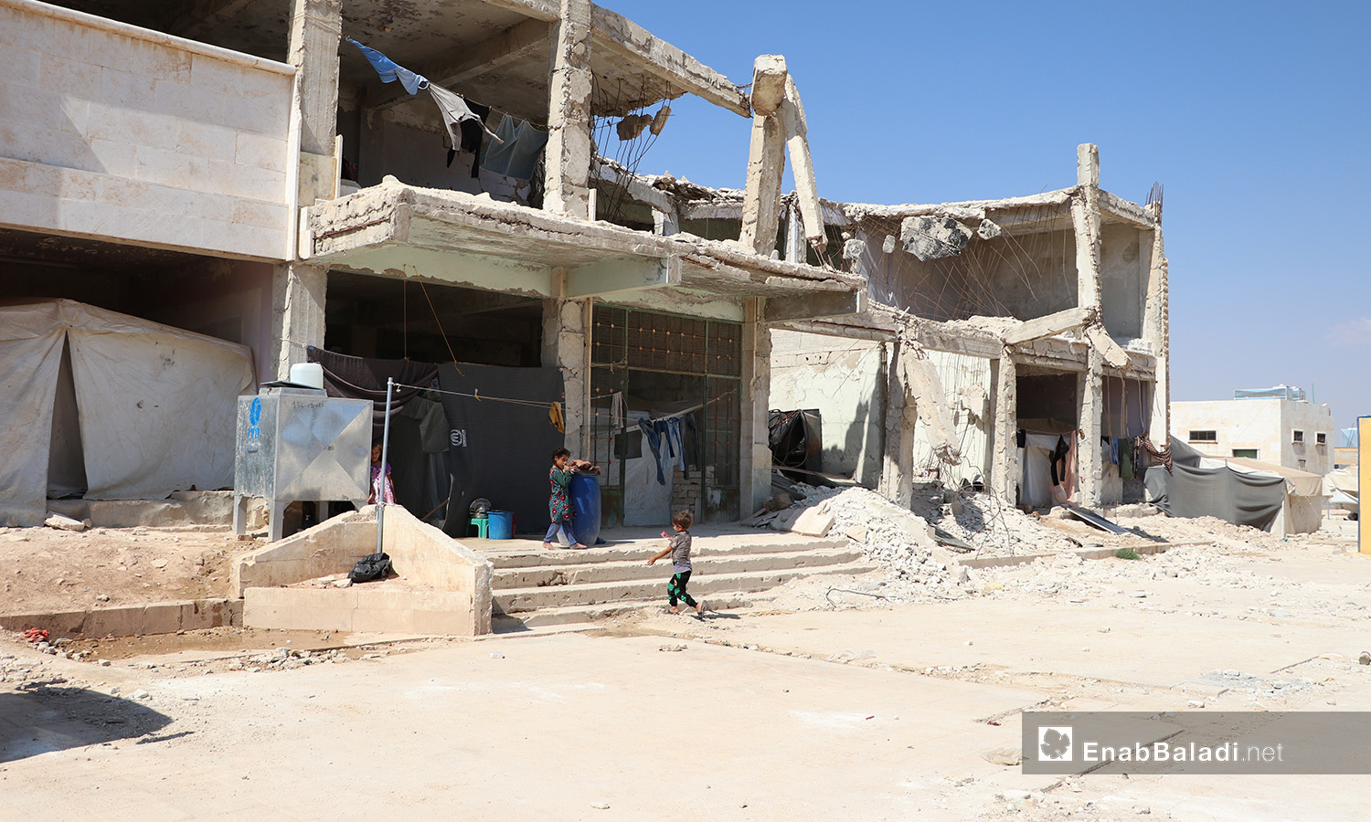 """Displaced people live in a partially destroyed house in """"Qubtan"""" camp near the town of Akhtarin in the northern countryside of Aleppo - 17 July 2020 (Enab Baladi / Asem al-Melhem)"""
