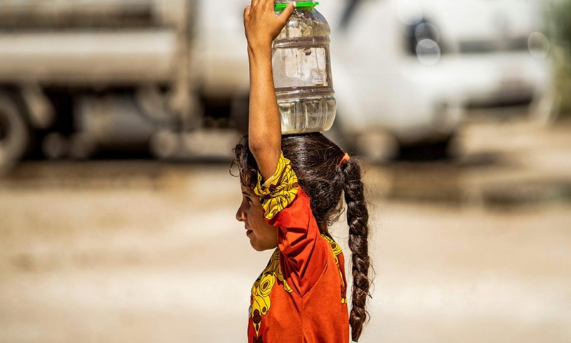 A displaced Syrian child carrying water to her camp in the city of al-Hasakeh, northern Syria - 24 August 2020 (France Press)