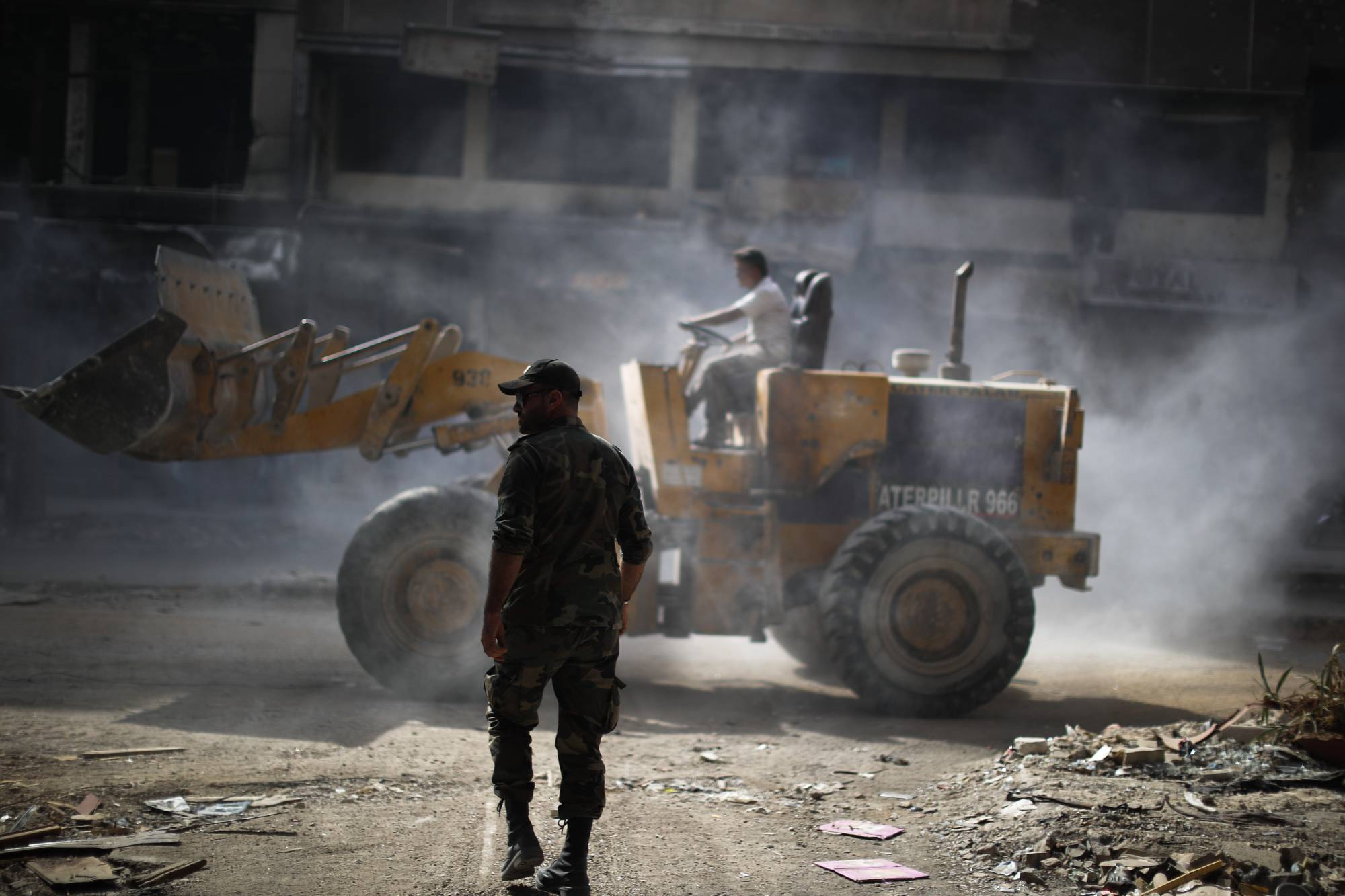 A Syrian soldier directs a bulldozer while removing rubble from the Yarmouk camp streets in Damascus – 6 October, 2018 (AP)