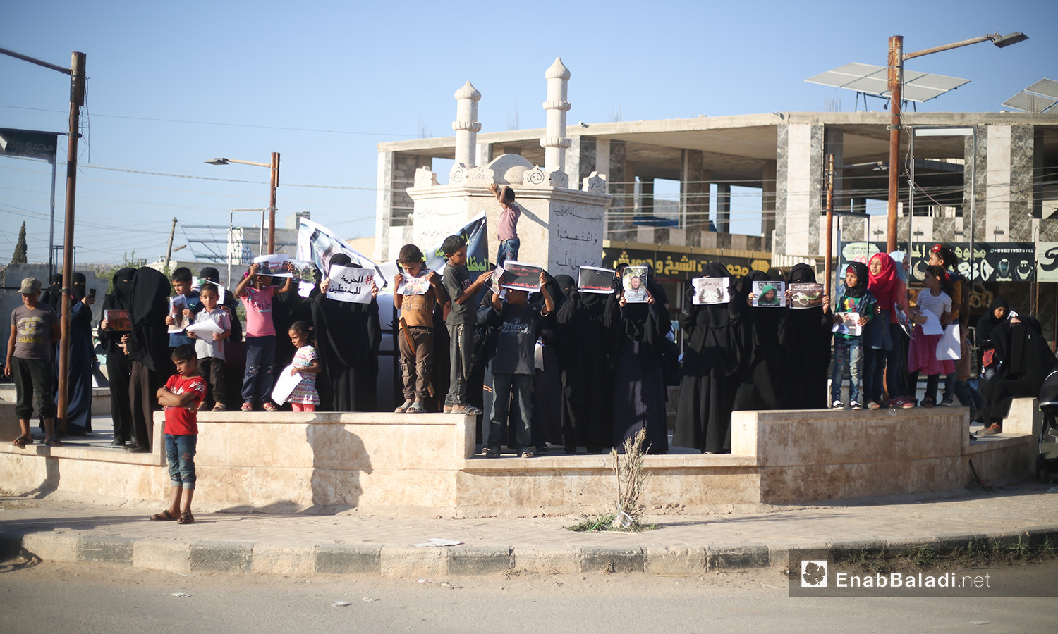 """A protest stand demanding the release of the British aid worker Tauqir Sharif, known as """"Abu Hussam the British"""" and the American journalist Darrell Lamont Phelps, nicknamed """"Bilal Abdul Kareem"""" in Atmeh of Idlib countryside – 20 August 2020 (Enab Baladi / Yousef Ghuraibi)"""