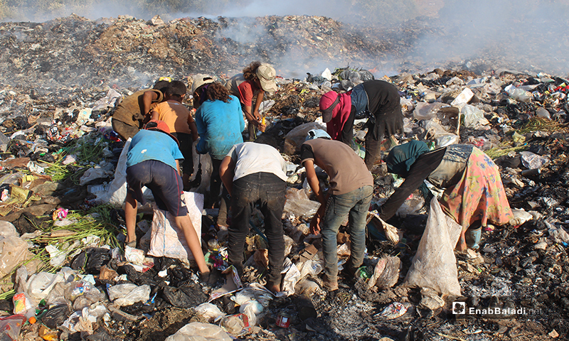 Children, women, and men collecting scrap materials from a waste dump near the town of Qah on the Syrian-Turkish border - 1 August 2020 (Enab Baladi)