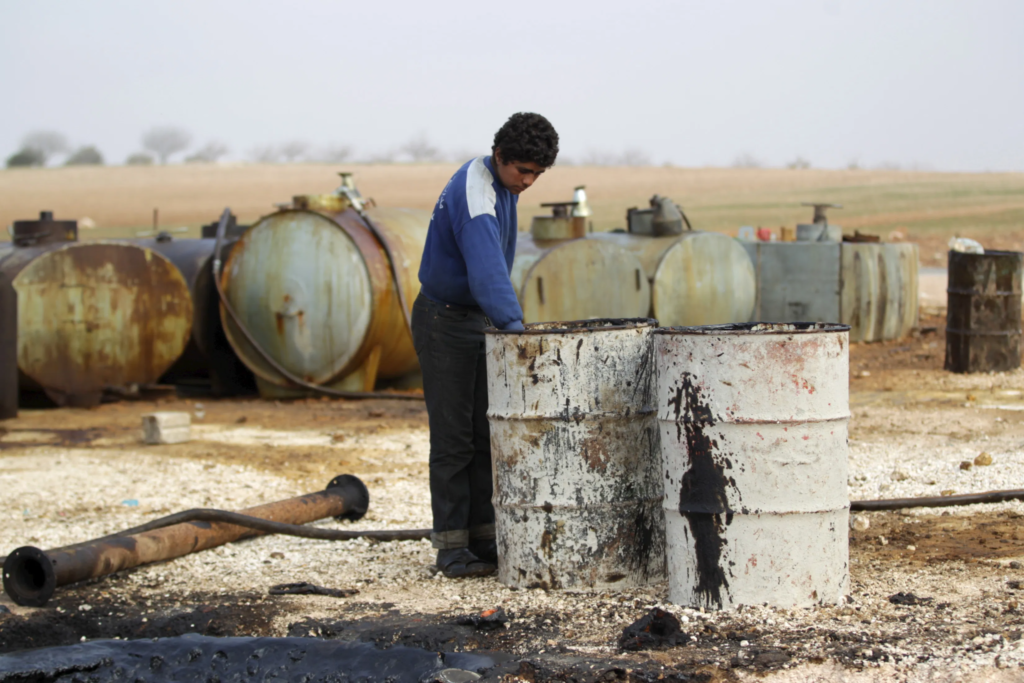 A young man working at a rudimentary oil facility in the town of Marmarin in Idlib – 21 November 2018 (Reuters)