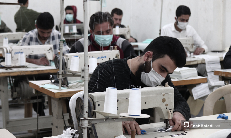 Workers in a factory for manufacturing protective face masks in the city of Idlib - 29 March 2020 (Enab Baladi/Youssef Gharib)