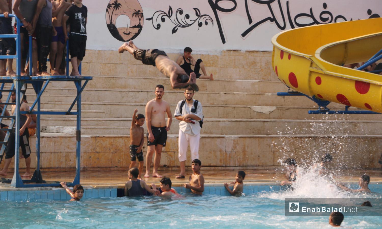 People swimming at Idlib's municipal swimming pool after the rise in temperatures – September 2020 (Enab Baladi / Anas al-Khouli)