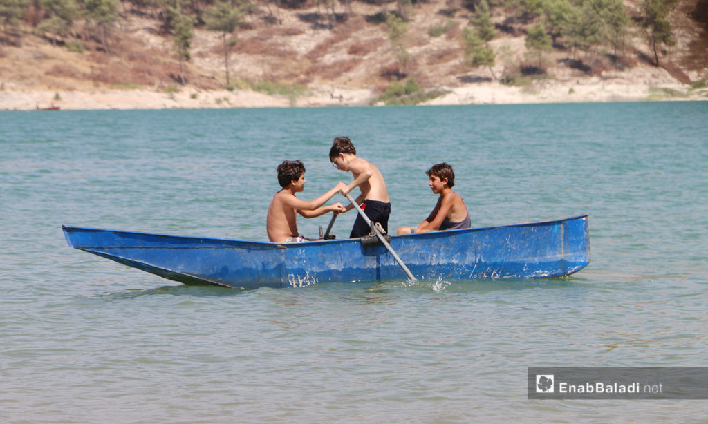 Children rowing a boat on Maidanaki Lake in Afrin, Northern Syria - 21 July 2020 (Enab Baladi / Abd al-Salam Majaan)