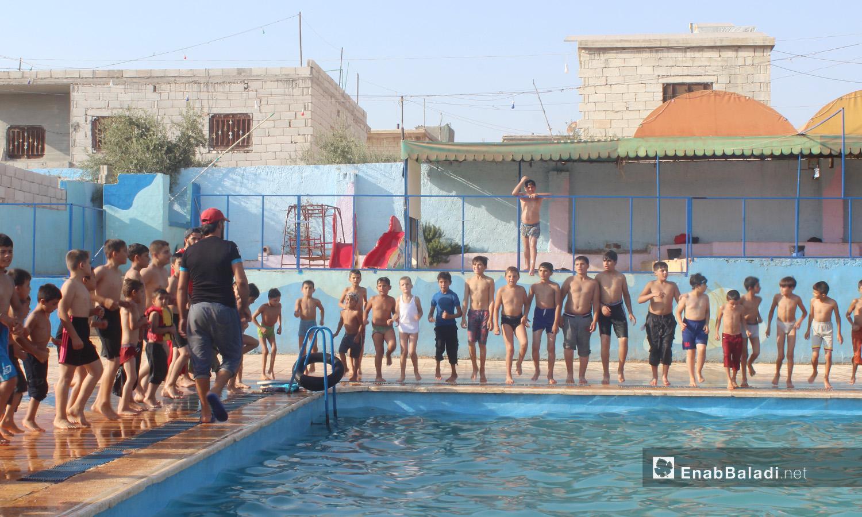 "Children preparing to begin their swimming practices in the ""al-Iradeh"" swimming pool in Killi town in northern Idlib countryside – September 2020 (Enab Baladi / Iyad Abdel Jawad)"