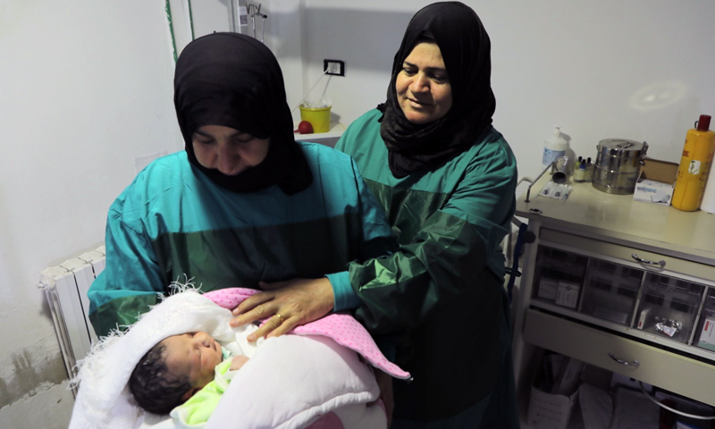 A doctor at UOSSM Hospital in the town of Ariha holding a newborn baby - 6 August 2020 (UOSSM)