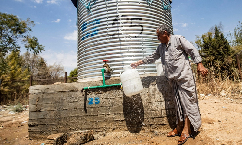 A Syrian man filling drinking water from water tanks provided by Syrian organizations during water -cuts in al-Hasakah, North-eastern Syria - 22 August 2020 (AFP)