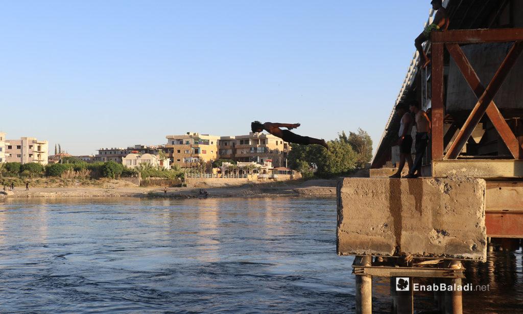 A young man jumping to swim from a bridge crossing the Euphrates River in Raqqa Governorate – 24 July 2020 (Enab Baladi / Abdulaziz Saleh)
