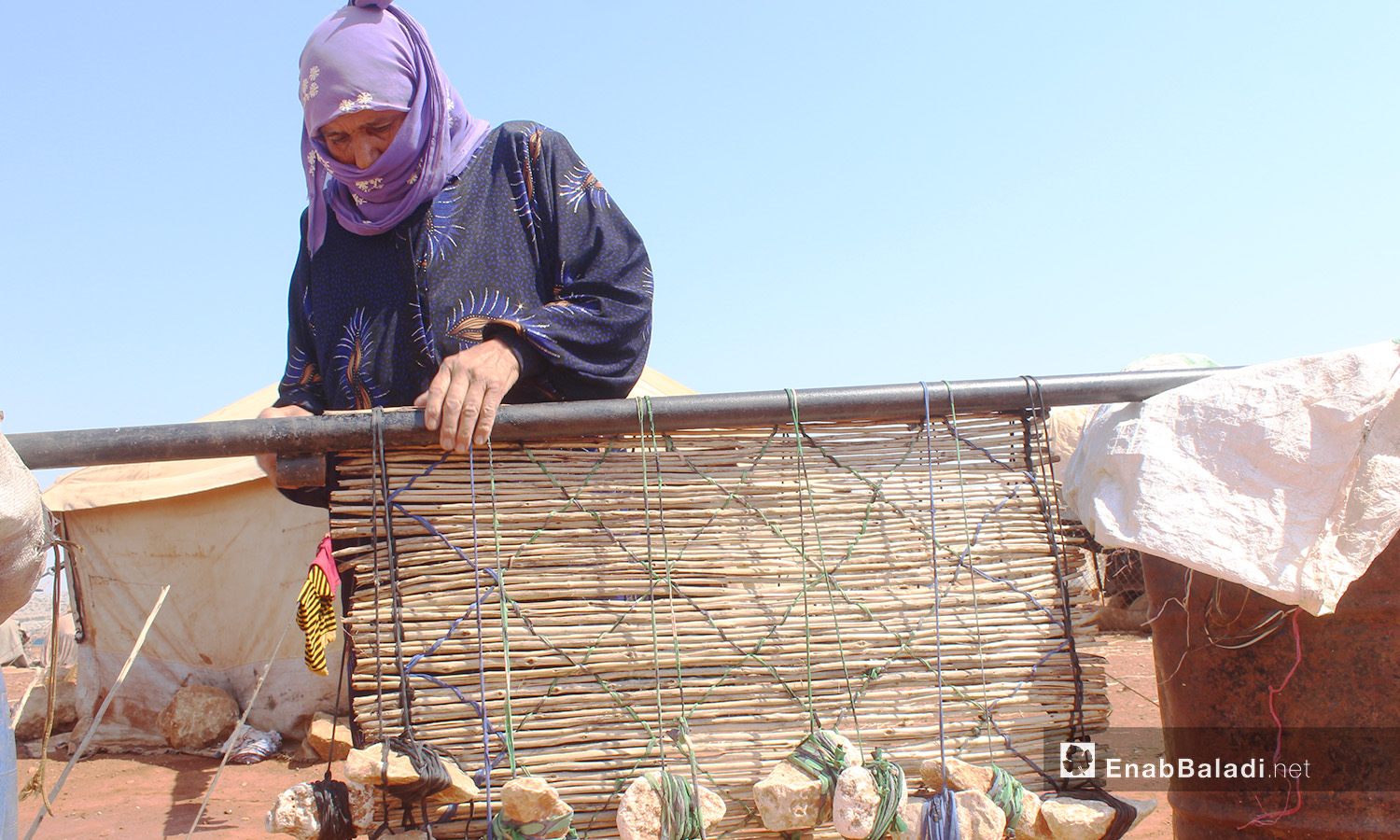 """Um Mohammed while making mats that are locally known as """"al-Zarb"""" after combining """"al-Zal"""" cane sticks together – 28 August 2020 (Enab Baladi / Iyad Abdel Jawad)"""