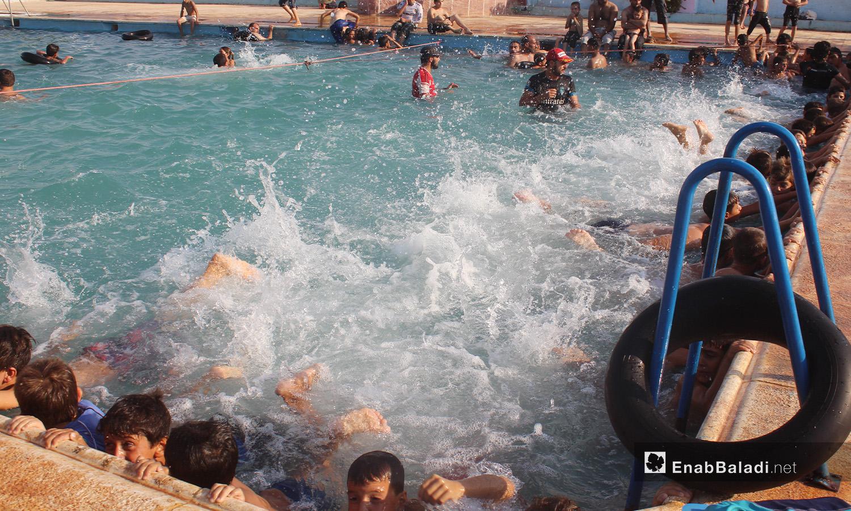 "Children practicing swimming in the ""al-Iradeh"" swimming pool in Killi town in northern Idlib countryside – September 2020 (Enab Baladi / Iyad Abdel Jawad)"