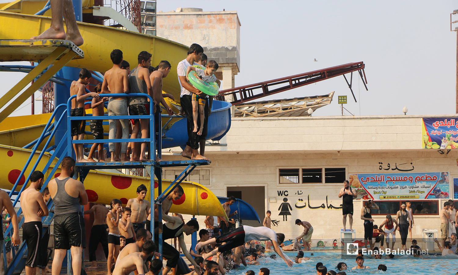 Crowds of children and young men who want to jump in Idlib's municipal swimming pool - September 2020 (Enab Baladi / Anas al-Khouli)