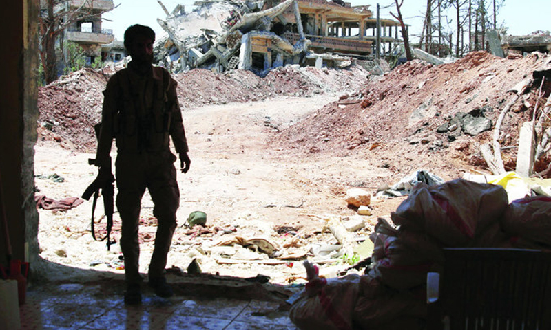 A fighter carrying a weapon, and behind him destroyed buildings in Daraa, southern Syria (Reuters)