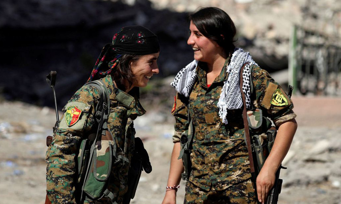 Kurdish fighters waving flags in Tell Abyad - 2015 (Reuters)