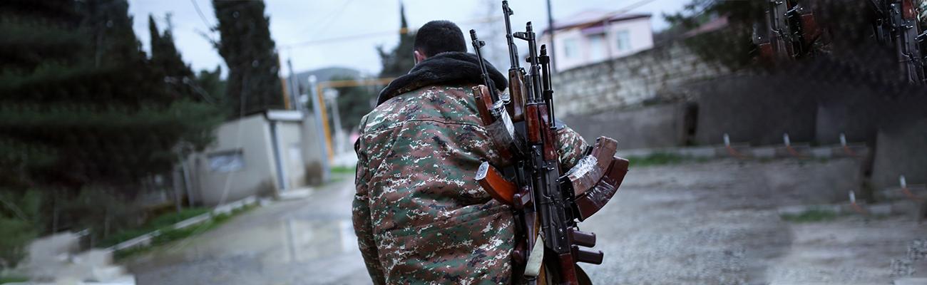 A fighter carrying multiple Kalashnikovs