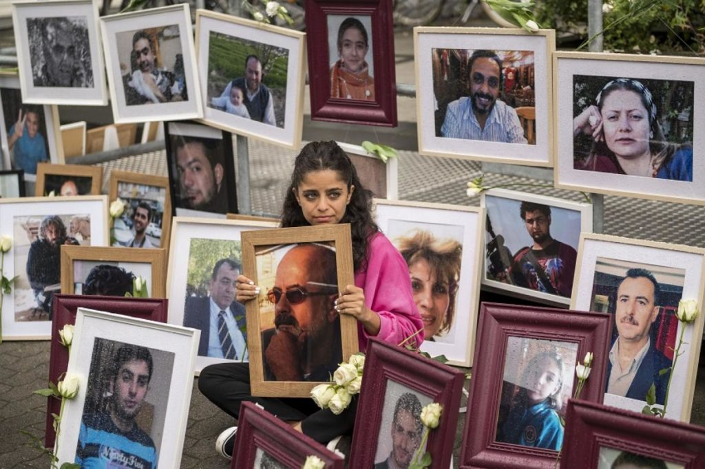 A Syrian activist Wafa Mustafa sits amongst photos of victims of Syrian regime, holding a picture of her detained father, during a protest outside the trial of two former Syrian intelligence officers accused of committing crimes against humanity in Koblenz, western Germany - 4 June (Thomas LOHNES / AFP)