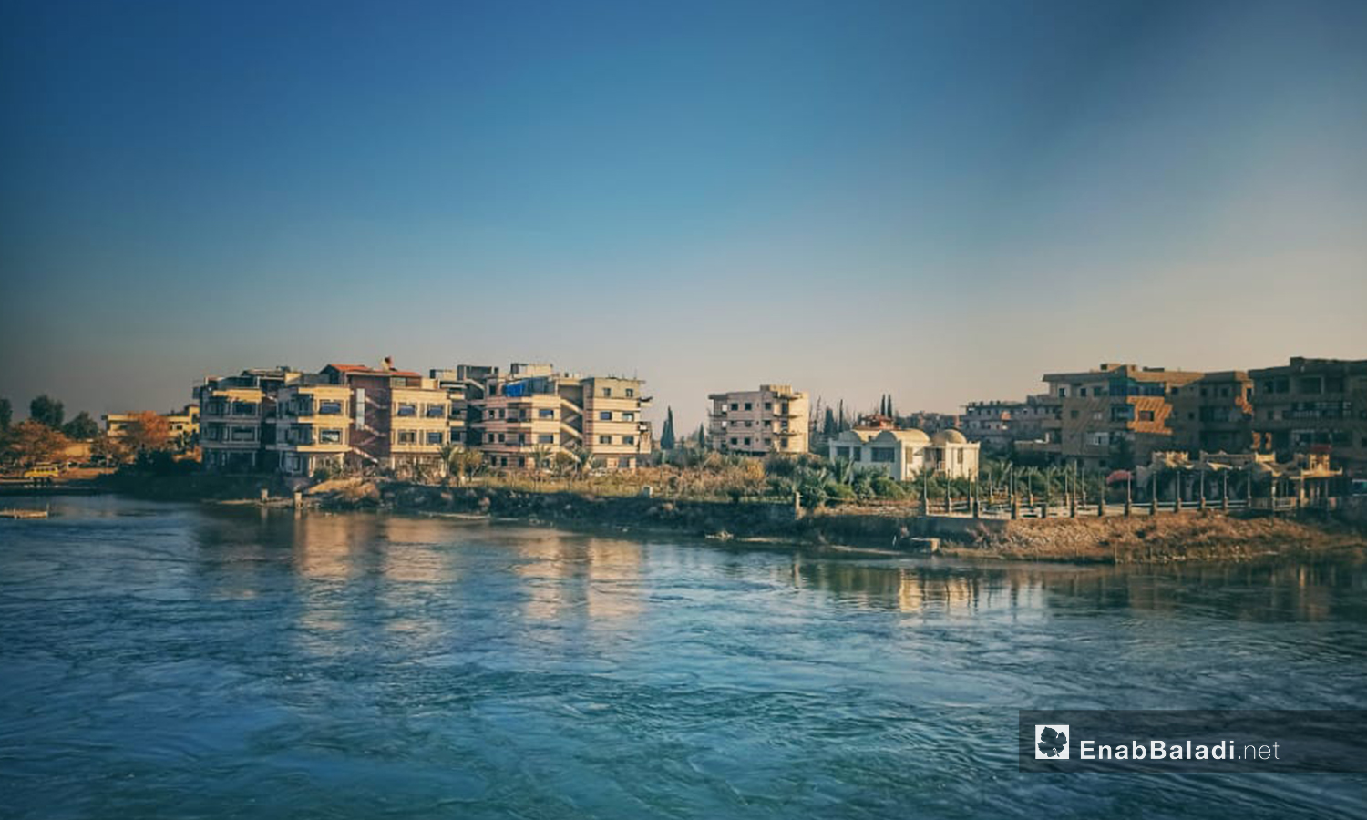 Residential buildings overlooking the Euphrates River in al-Raqqa city, northern Syria - 09 July 2020 (Enab Baladi)