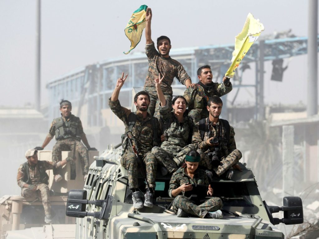 SDF members riding on a tank during the operations to control Raqqa (Reuters)