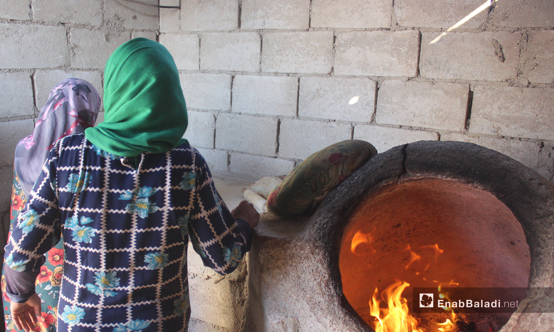 Women baking flatbreads in a tandoor oven in the village of killi in the northern countryside of Idlib - October 2020 ((Enab Baladi / Iyad Abdel Jawad) )
