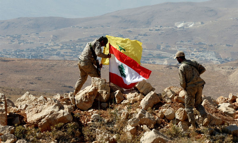 Fighters placing the Lebanese flag next to Hezbolla's flag in Jrood Arsal - 25 July 2017 (Reuters)
