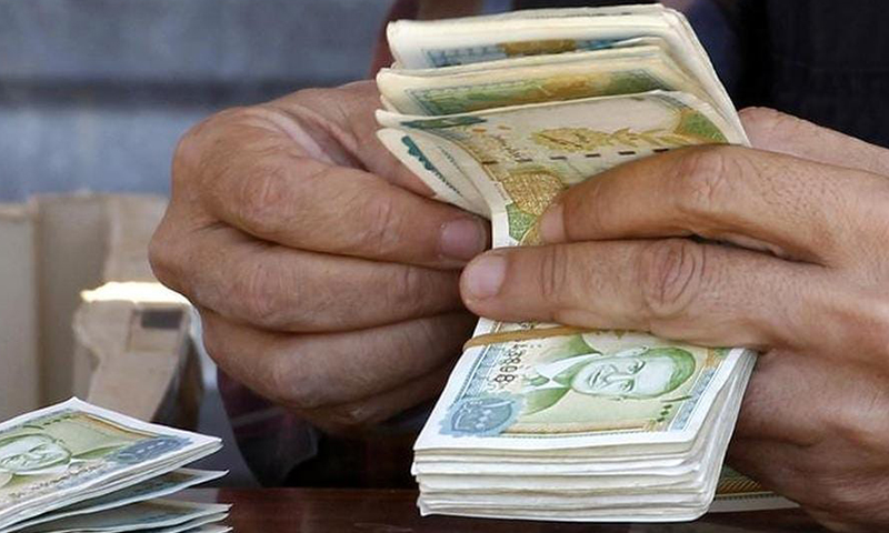Hands of a man collecting money from the Syrian currency (An expressive image)