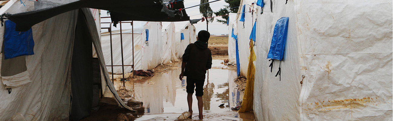 Caption 1: A child wading in the water that flooded the Falah camp in the northern countryside of Aleppo, which lacks adequate equipment for facing winter rains - 4 November 2020 (Enab Baladi - Abdul al-Salam Majaan)