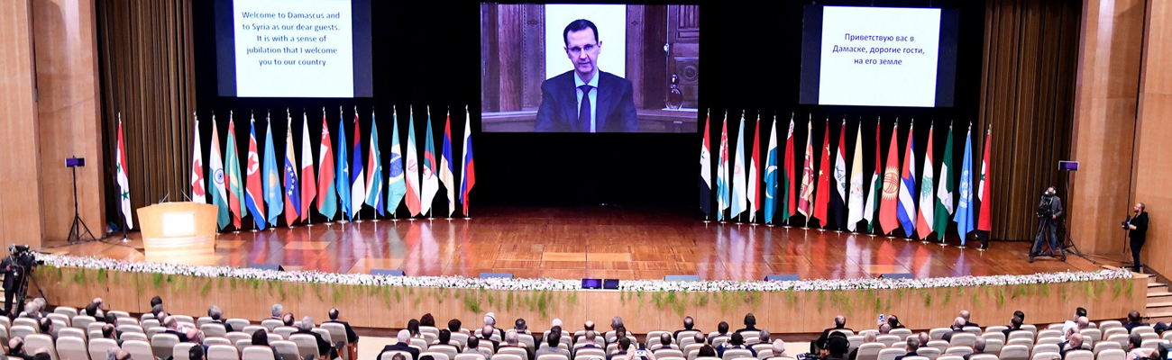 """The head of the Syrian Regime addresses the audience via a video call due to the spread of """"Covid-19"""" during the """"refugees return"""" conference in the Syrian capital, Damascus under the supervision and organization of Russia - 11 November 2020 (Syrian News Agency """"SANA"""")"""