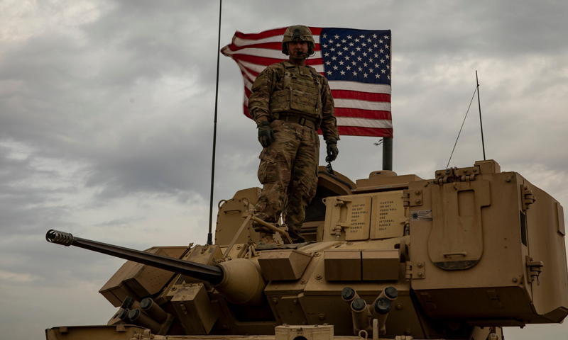 A soldier from the International Coalition Forces (ICF) standing on an armored vehicle with the American flag behind him - 24 November 2020 (International Coalition)