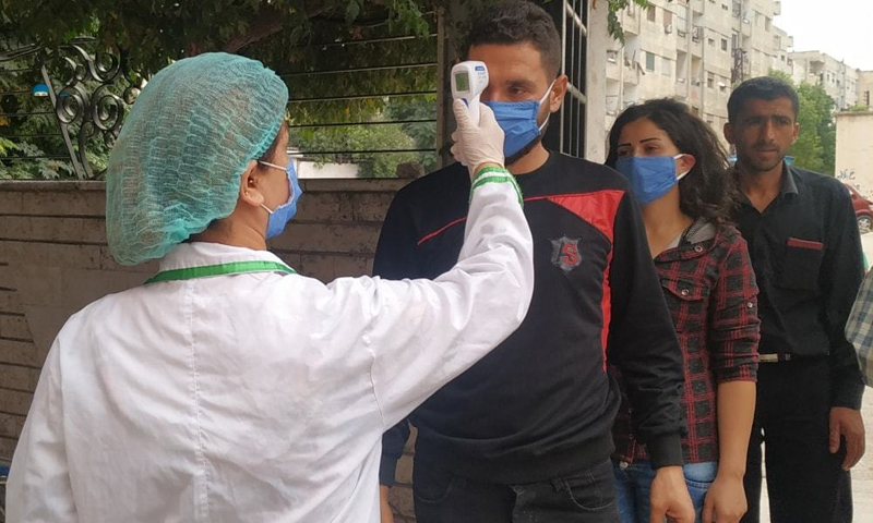 Wearing masks, people lined up for temperature checks before entering the Bassel Hospital as a part of the coronavirus preventive measures.