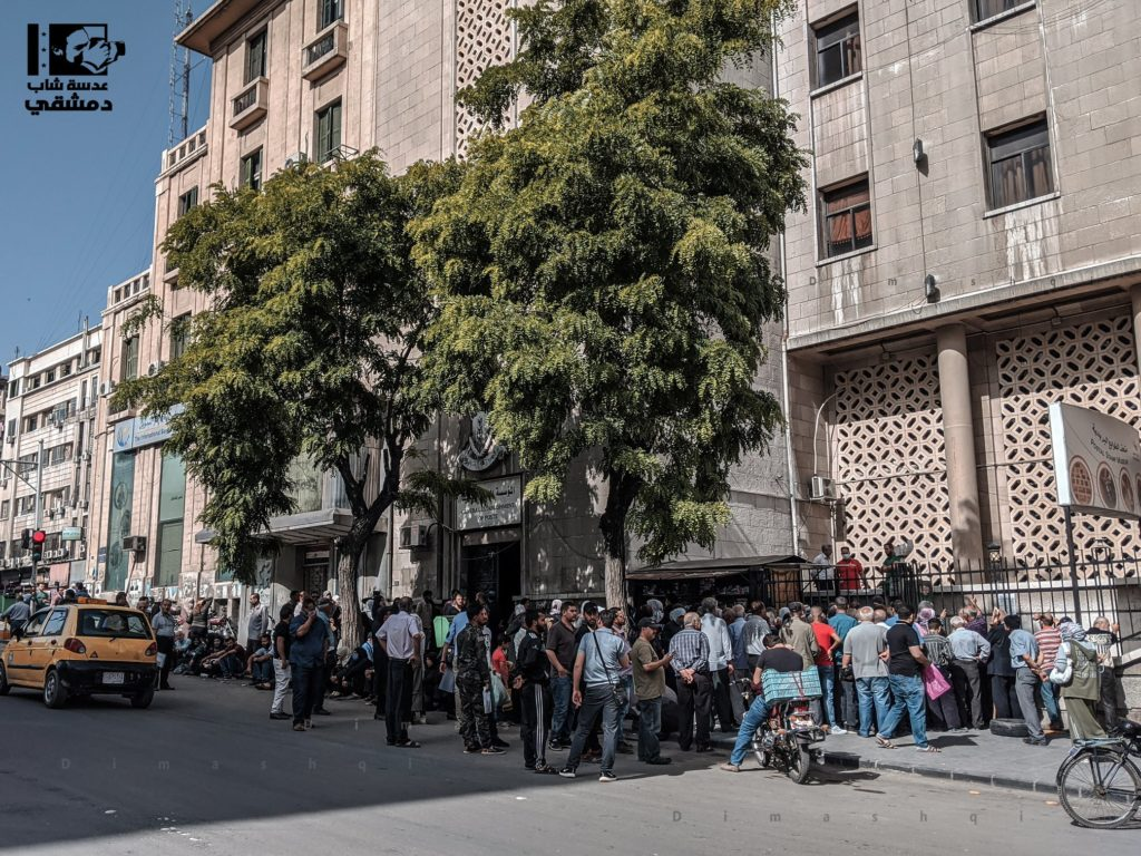 Syrian employees waiting to receive stamps to obtain a grant given to state institutions employees who had been suspended due to the spread of COVID-19 in Damascus - May 2020 (Lens of a young Damascene)
