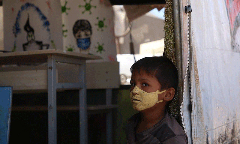 """A child with a protective mask against the novel coronavirus painted on his face in the """"al-Anwar"""" displacement camp, west of Maraat Misrin, northwestern Syria- 16 September 2020 (AFP/ Muhammad al-Rifai)"""