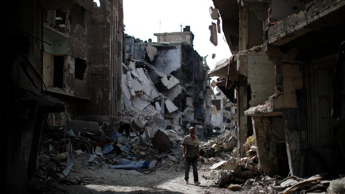 A man walks through rubble in the Palestinian refugee camp of Yarmouk in the Syrian capital Damascus - 06 October 2018 (AP)