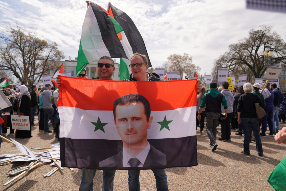 Washington, DC/USA, two demonstrators holding a Syrian flag super imposed with the image of President Bashar al-Assad at an anti-AIPAC demonstration at the White House – 24 March 2019 (Shutterstock)