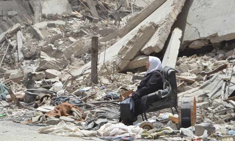 A woman sitting amidst the debris of destroyed buildings in the Yarmouk refugee camp- 2018 (Yarmouk Camp News)