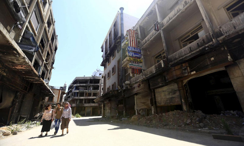 Women walking in a destroyed neighborhood in the Old City of Homs - 3 June 2015 (Reuters)
