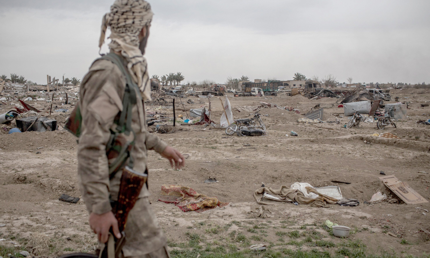 An SDF fighter walking in the middle of al-Baghuz town after the end of the battles with the so-called Islamic State - April 2019 (The Sun)