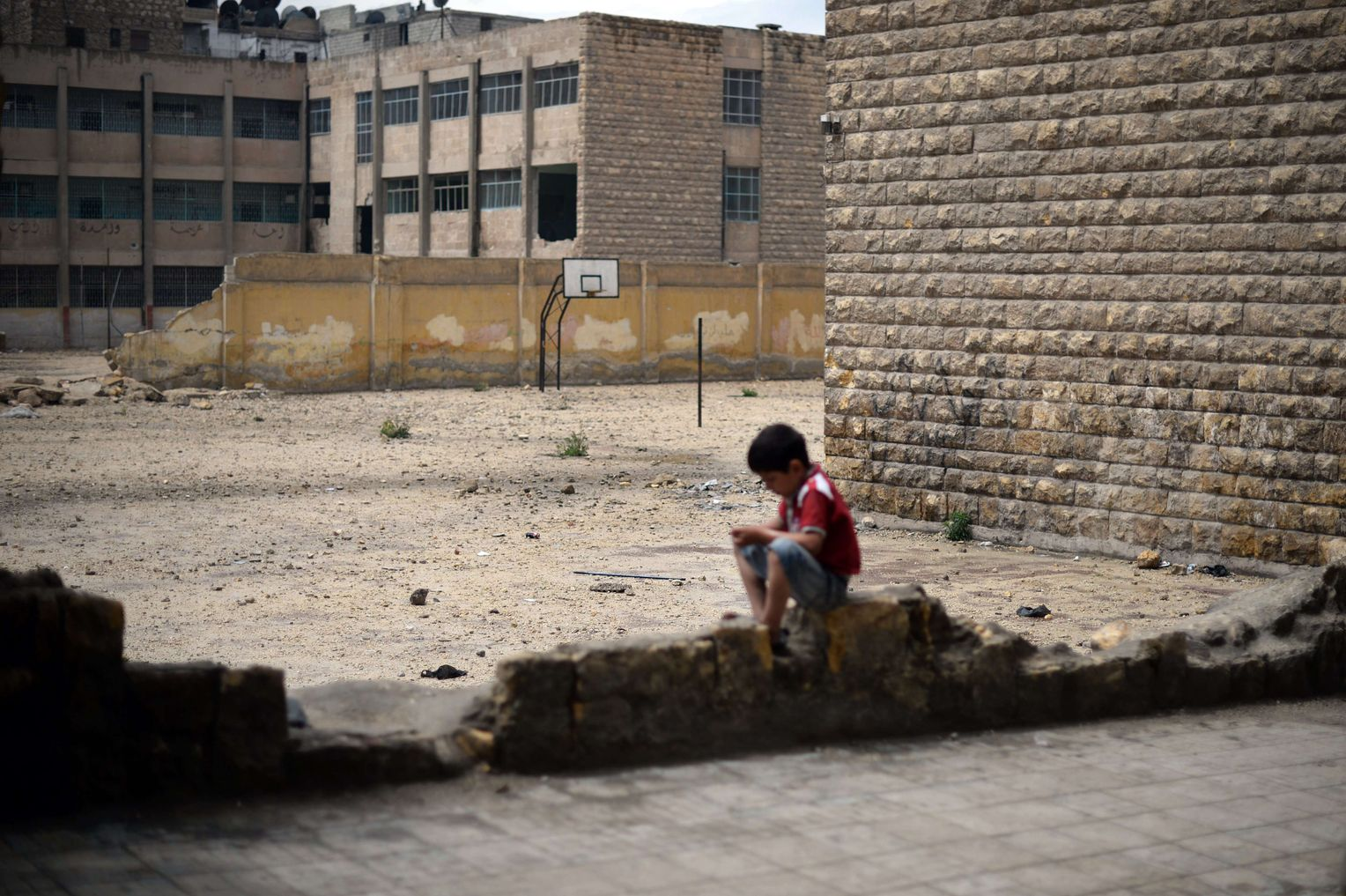 A Syrian child sitting near a school destroyed by the Syrian regime's bombing - 2013 (AFP)