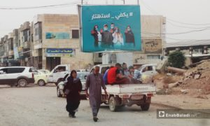 People walking in a street in al-Raqqa city and behind them appears an awareness billboard inviting people to abide by the coronavirus protective measures - September 2020 (Enab Baladi / Abdul Aziz al-Saleh)