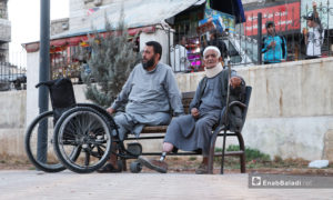 An old man with his crutch and prosthetic limb is resting on a public wooden chair next to a man whose leg is amputated and uses a wheelchair - 24 November 2020 (Enab Baladi / Asim Melhem)