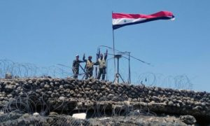 Regime forces soldiers making the victory sign next to the Syrian regime's flag in Tell al-Harrah on the highest hill in the southwestern governorate of Daraa - July (AFP)