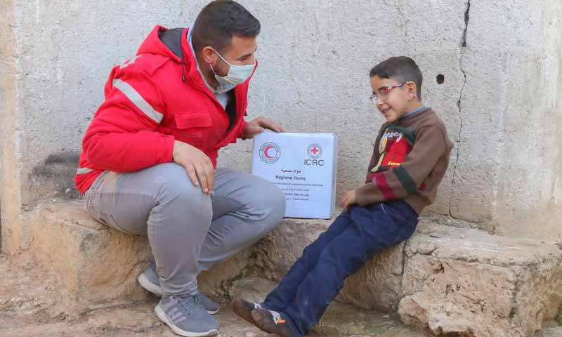 A Syrian Red Crescent worker provides medical supplies to a child in the governorate of Daraa to contain coronavirus- 17 December 2020 (Syria's Red Crescent Daraa branch)